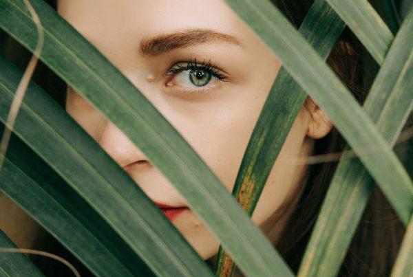Woman looking through palm frawns