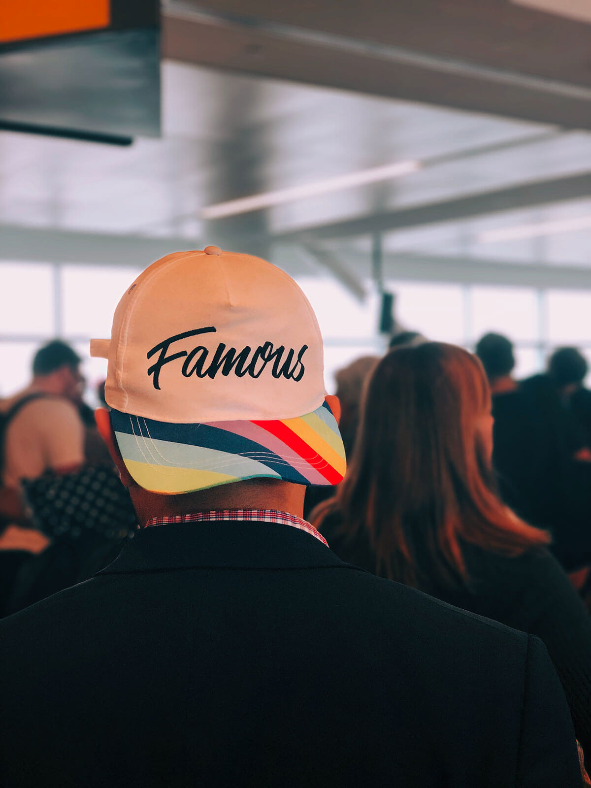 Man in a crowd wearing a white hat with the word 'Famous' printed on it.