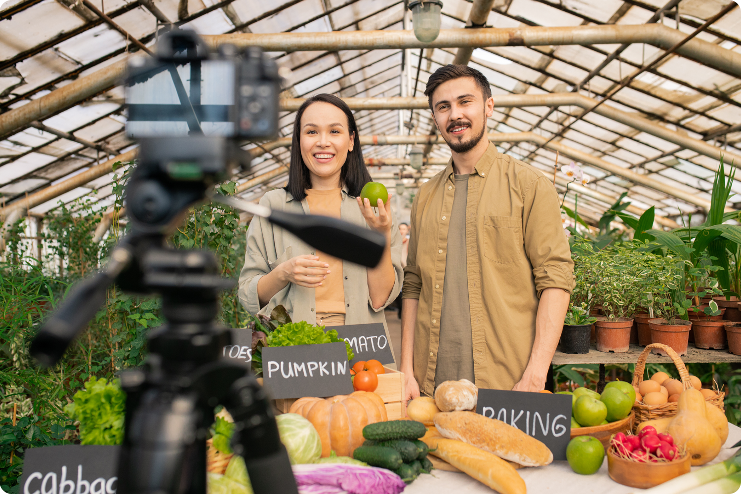 Man and woman being filmed displaying produce