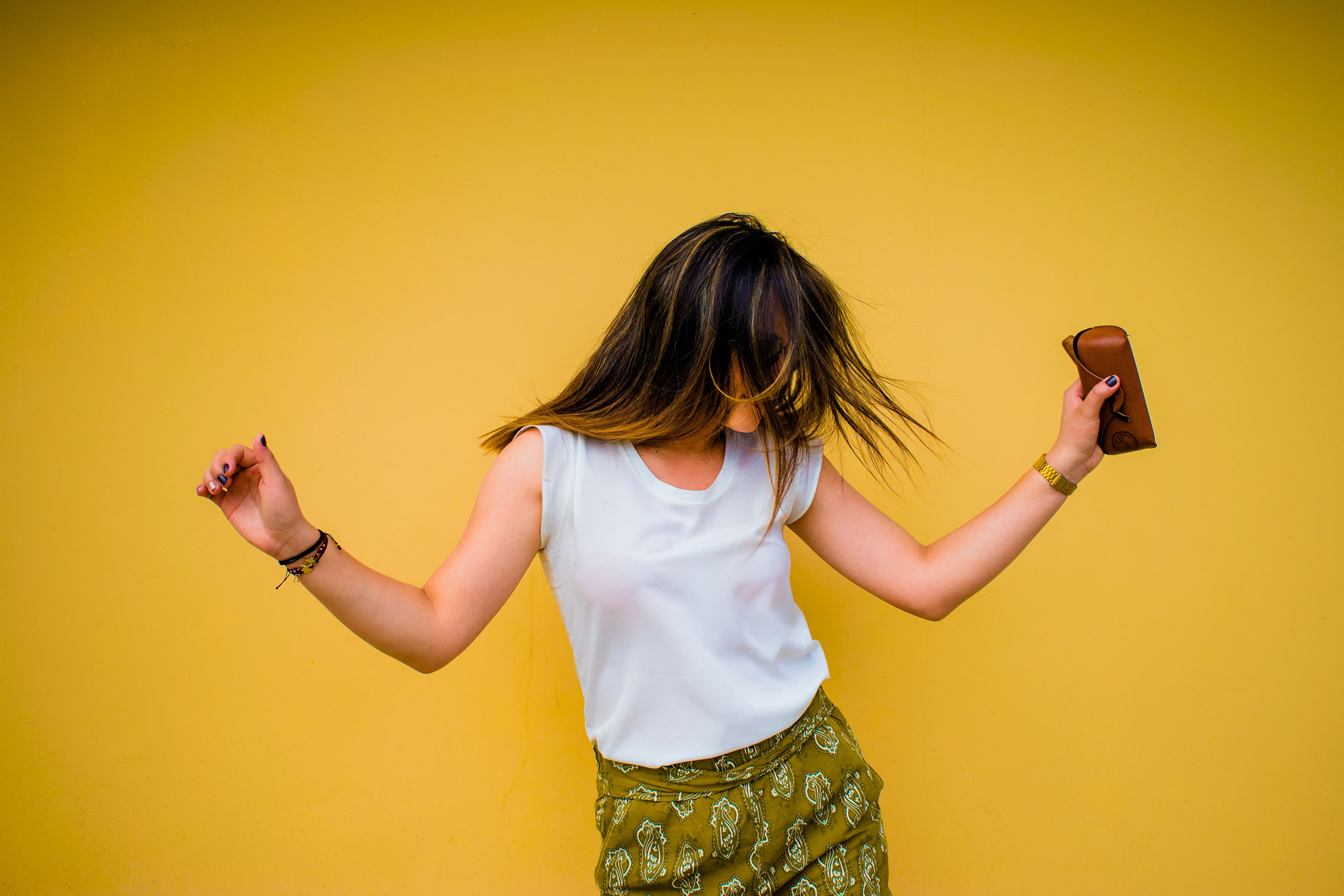 Girl dancing on yellow backdrop