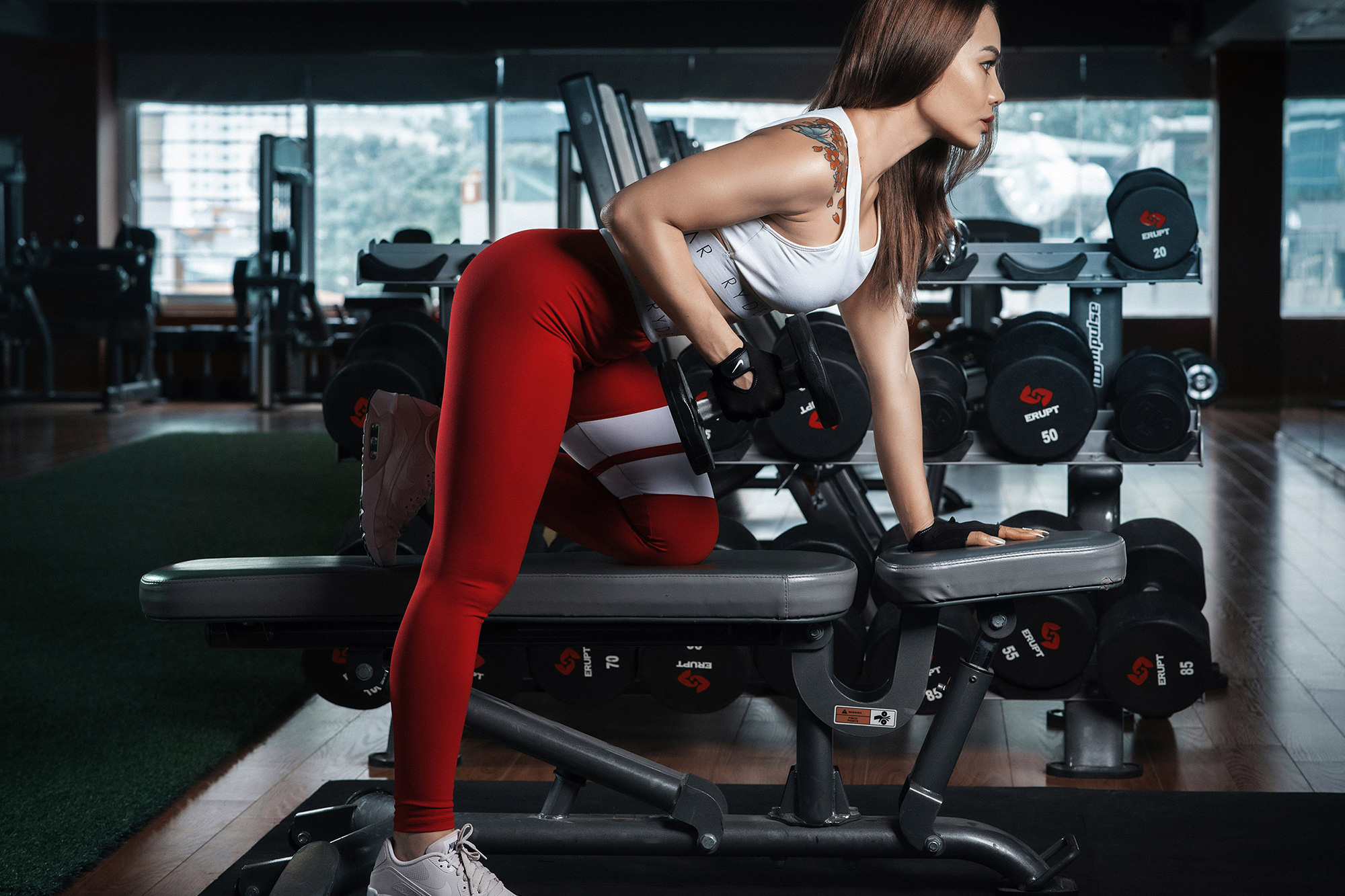 woman lifting weights kneeling on workout bench