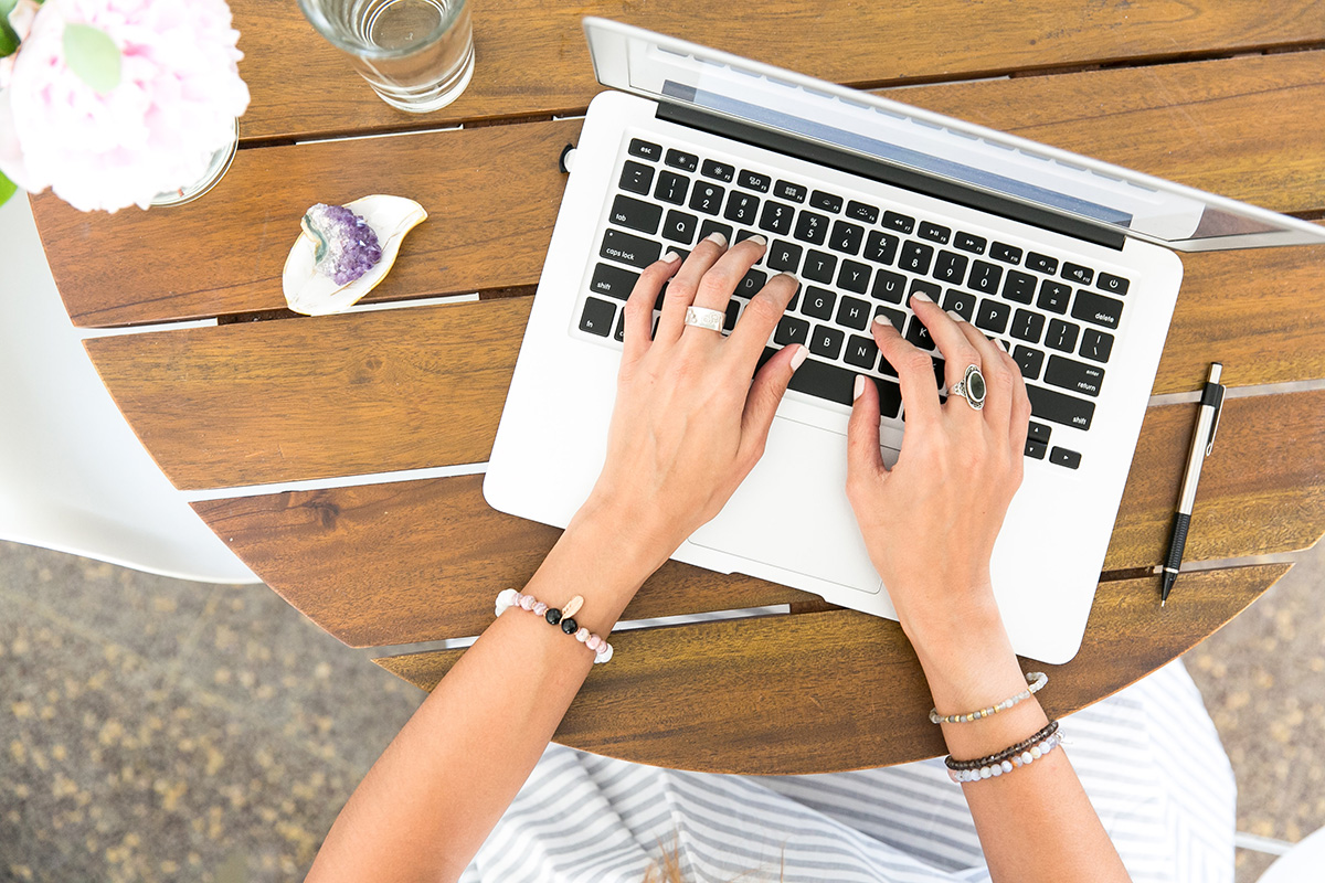 female blogger writing a blog post on wooden table