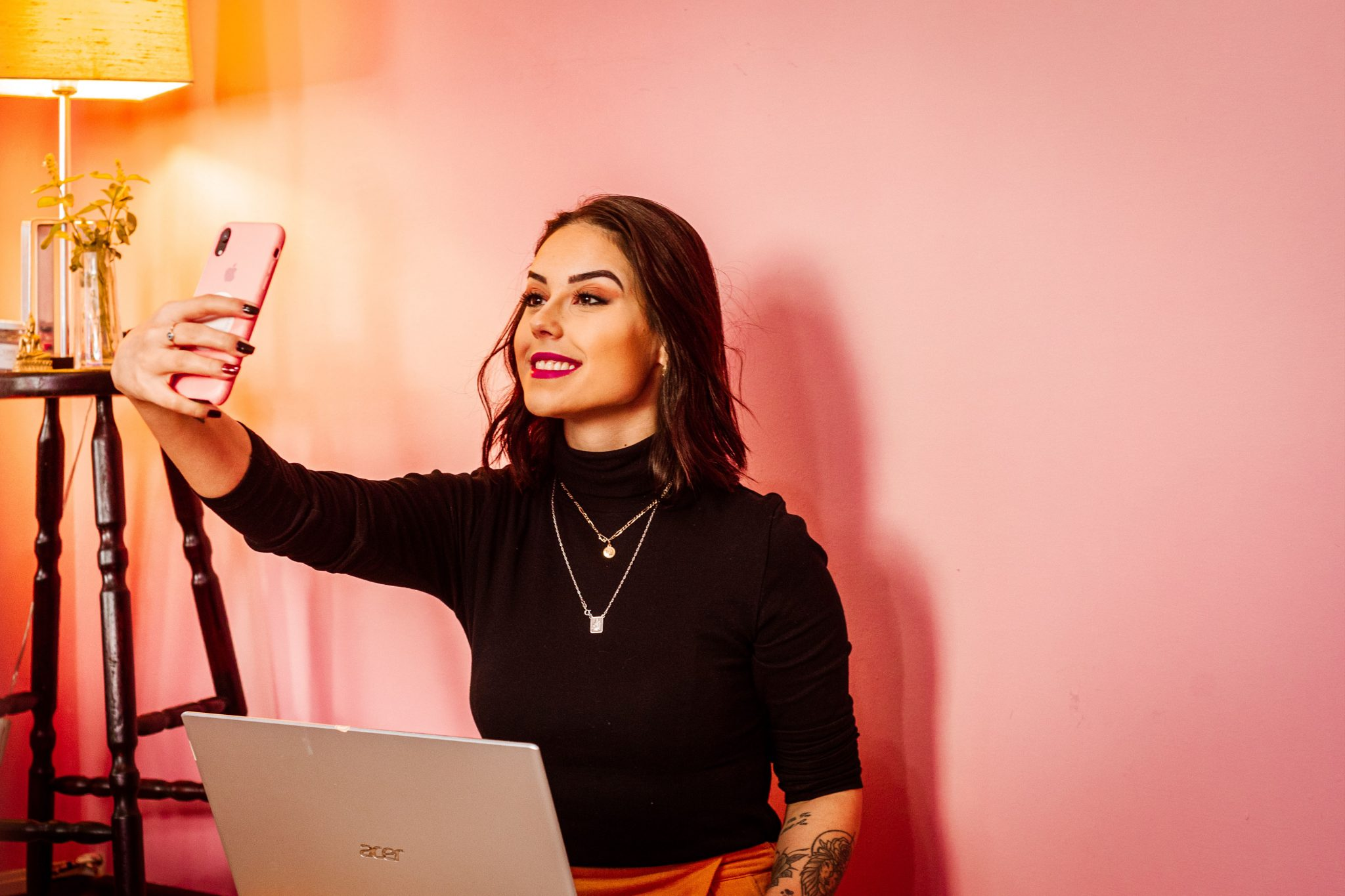 Female social media influencer takes selfie with smartphone while sitting in front of her computer