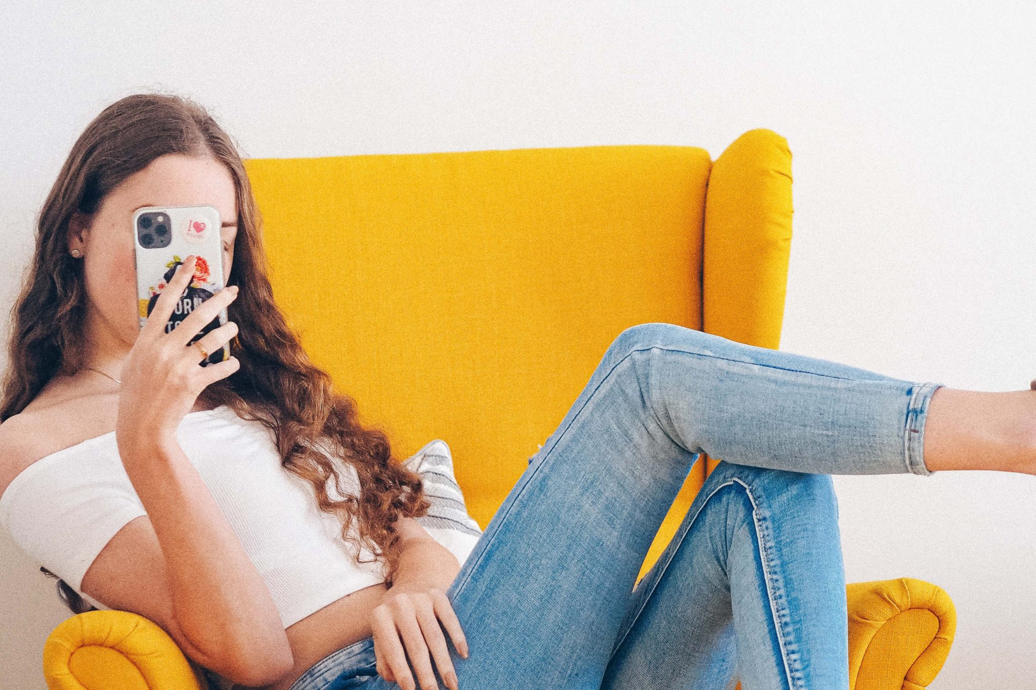 Gen Z aged female sitting on yellow armchair looking at smartphone
