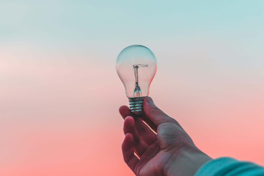 Hand holding light bulb against gradient background