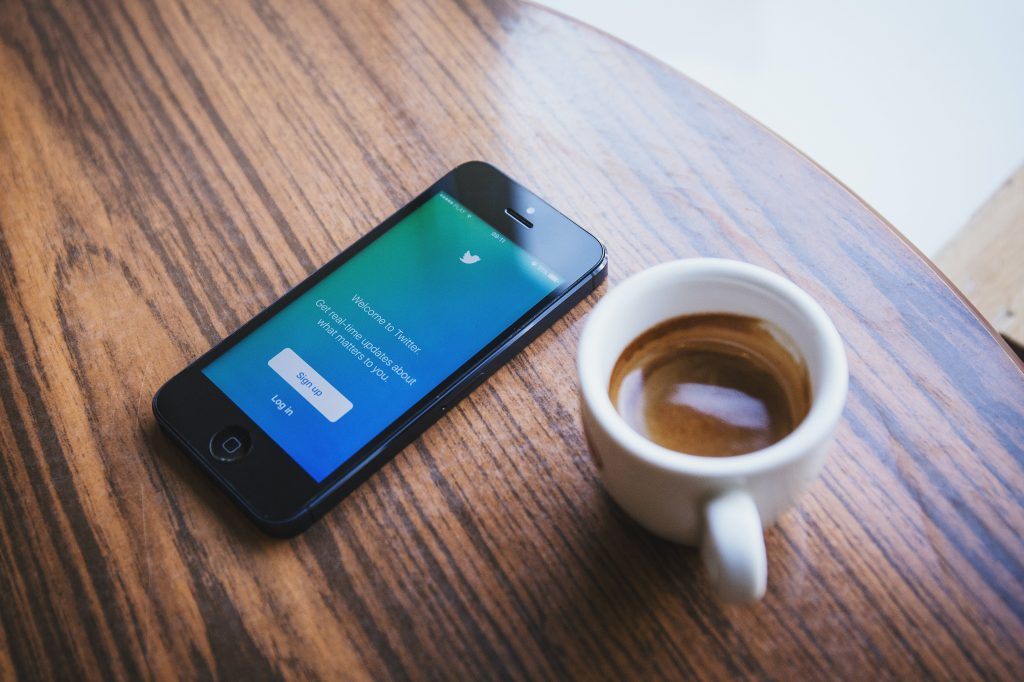 Twitter Fleets: Phone with Twitter app open next to cup of coffee on table.