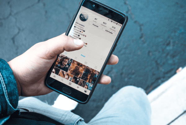 man holding smartphone looking at Instagram link in bio
