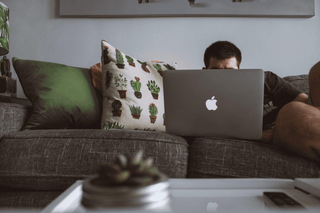 man on couch watching laptop to get more views on youtube