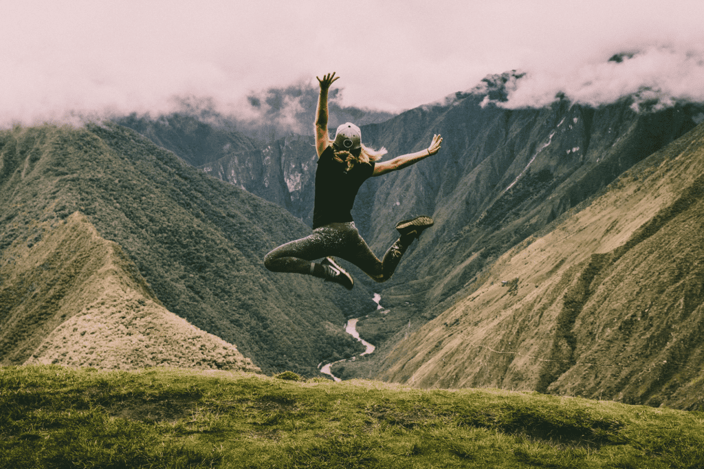 Woman leaping in mountain scene like raising influencer rates