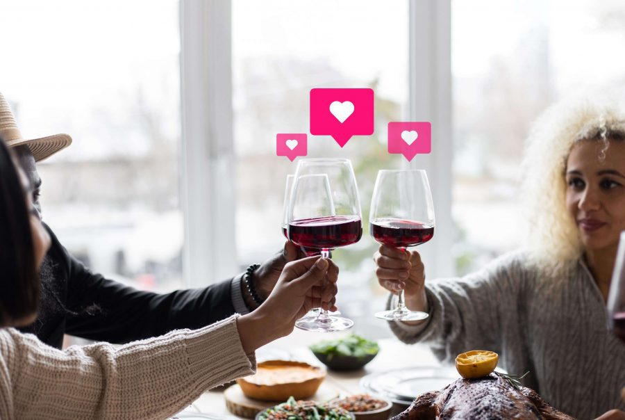 people clinking wine glasses with social hearts